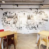 壁一面に描かれた壁画は当社の商いの原点と言える食をヨネヤマファームとして表現しています。